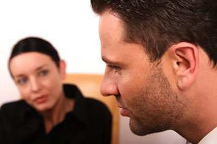 A close up picture of a man with a dark haired woman blurred in the background listening