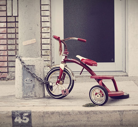 Childs tricycle chained to a light post