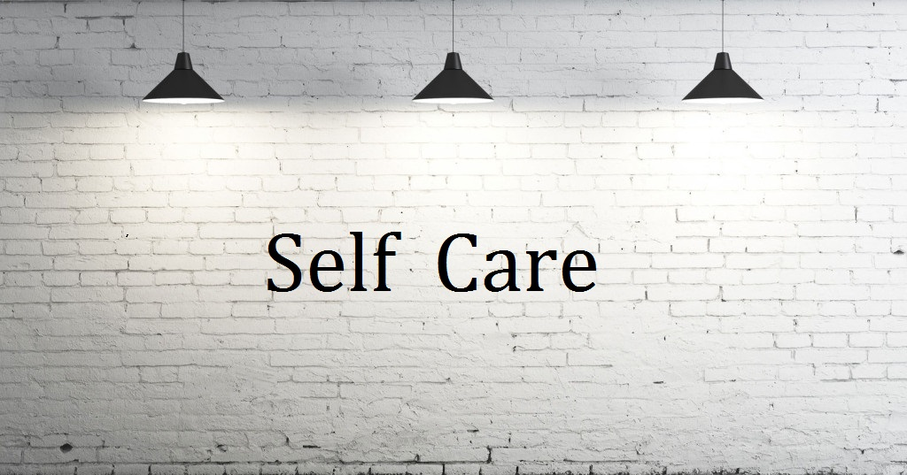 Image of white wall with lights with Self Care writteb